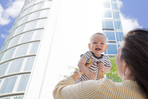 Mother lifting up her baby boy in the city - IHF00399
