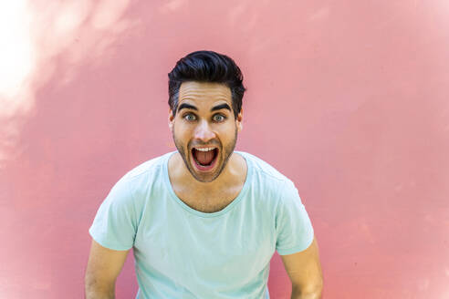 Happy man with open mouth against pink wall - AFVF06904