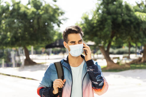Man wearing face mask talking on phone in city during COVID-19 - AFVF06913