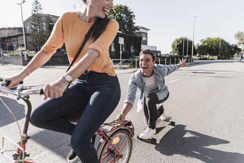 Cheerful young woman riding bicycle while boyfriend skateboarding on street in city - UUF20876