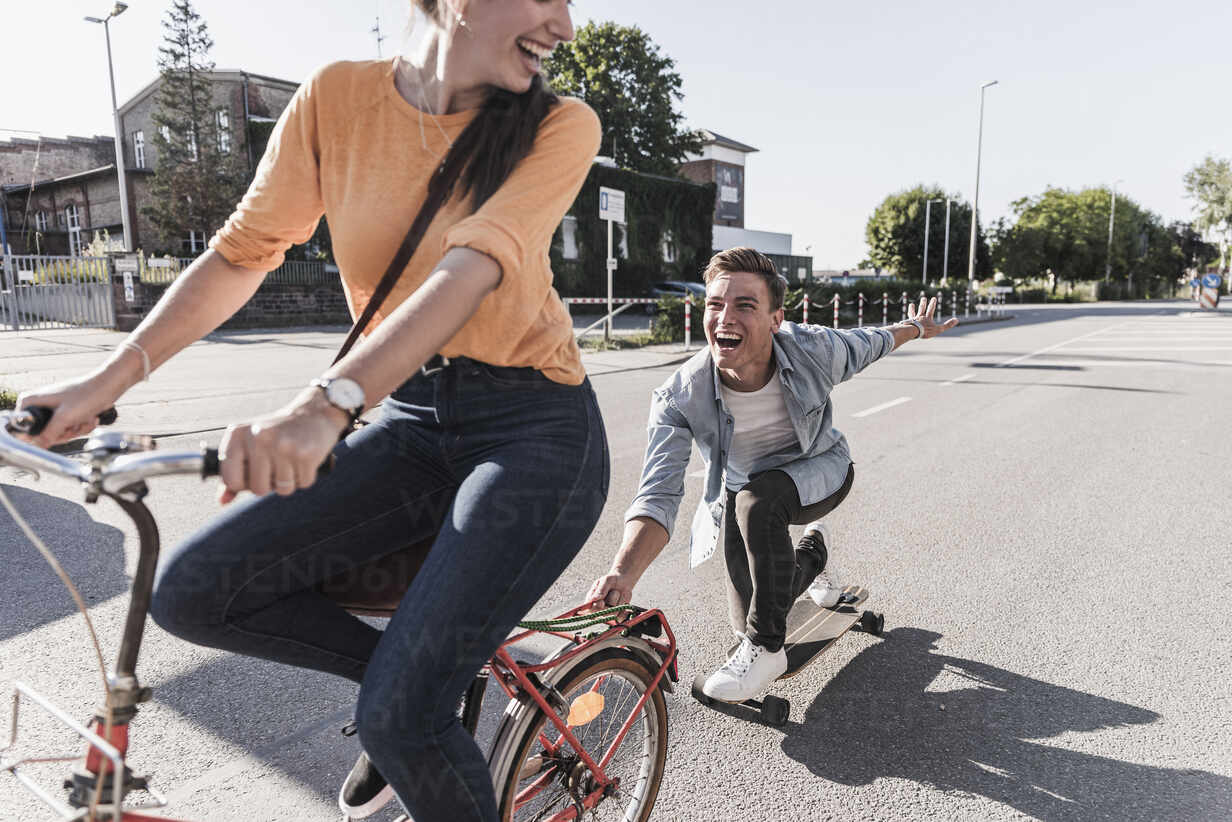 Cheerful young woman riding bicycle while boyfriend skateboarding on street in city - UUF20876 - Uwe Umstätter/Westend61
