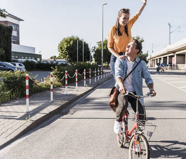 Happy woman standing with hand raised behind boyfriend riding bicycle on street in city - UUF20879