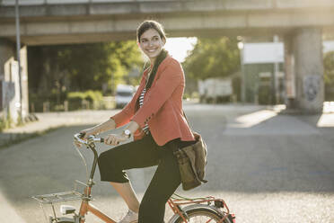 Smiling young woman riding bicycle on street in city - UUF20936