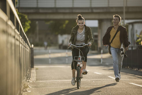 Cheerful boyfriend running behind girlfriend riding bicycle in city on sunny day - UUF20951