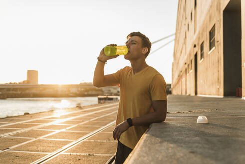 Man drinking water after workout against clear sky - UUF20963