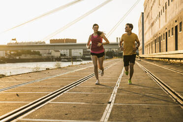 Smiling male and female friends jogging at harbor - UUF20966