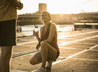 Smiling woman with water bottle looking at friend while crouching outdoors - UUF20969