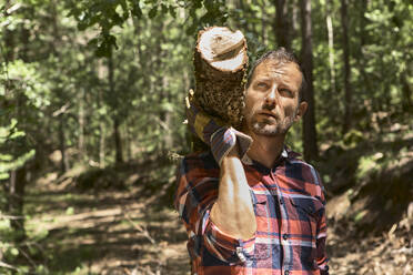 Thoughtful woodsman carrying log on shoulder while looking away in forest - VEGF02778