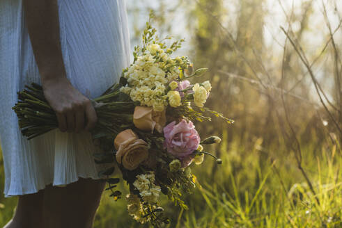 Woman holding flower bouquet while standing on field - DSIF00095