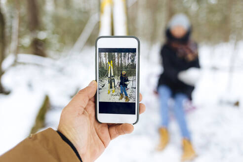 Man photographing girlfriend by skis through smart phone in forest during winter - KNTF05198