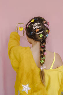 Teenage girl with various hair pins in her braid, holding smartphone with smiling emoji, rear view - ERRF04266