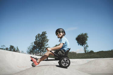 Little boy sitting on hoverkart at skateboard park during sunny day - HMEF01055