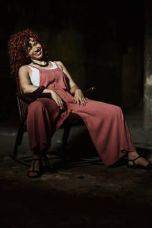 Smiling redhead woman sitting on chair in dark room - VEGF02784