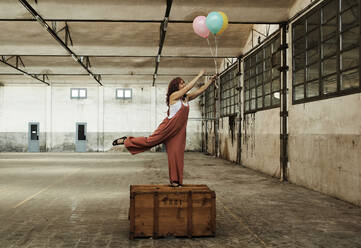 Cheerful woman enjoying with colorful balloons while standing on wooden box - VEGF02787