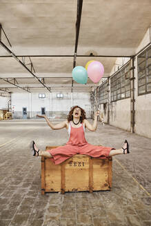 Cheerful woman playing with colorful helium balloons while sitting on wooden box - VEGF02790