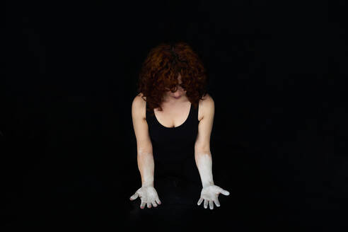 Woman with hands covered with white dust standing against black background - VEGF02793
