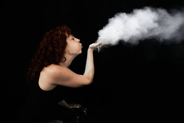 Woman blowing white dust while standing against black background - VEGF02796
