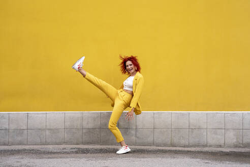 Energetic young woman in yellow suit running and jumping in front of yellow wall - VPIF02782