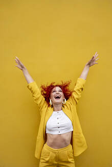 Exuberant young woman with red curly hair laughing in front of yellow wall - VPIF02791