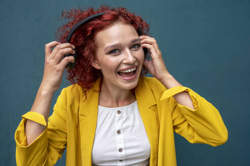 Young woman with red curly hair wearing headphones having fun listening music - VPIF02800