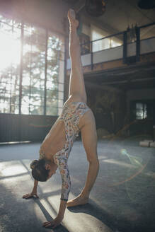 Side view of young female in colorful gymnastic costume stretching splits with leg raised up while training in modern ballet studio - ADSF11323