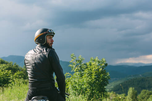 Young male motorcyclist on motorcycle looking over his shoulder, Florence, Tuscany, Italy - CUF56258