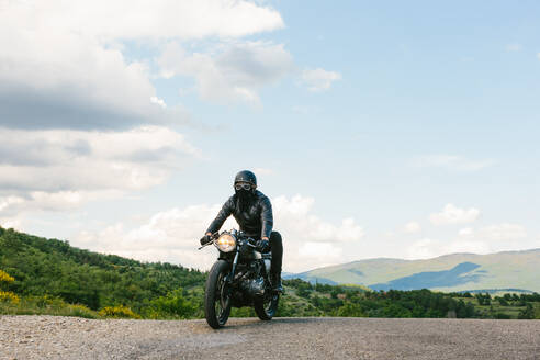 Young male motorcyclist on vintage motorcycle on rural road, Florence, Tuscany, Italy - CUF56270