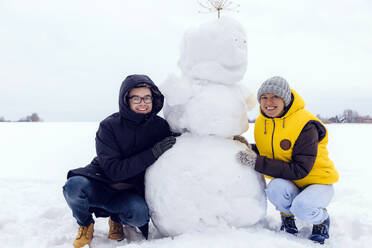 Smiling couple with snowman - KNTF05224