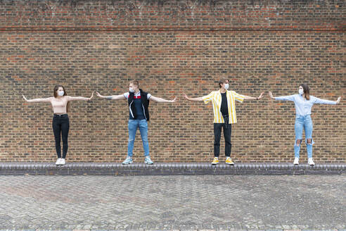 Male and female friends with arms outstretched maintaining safe distance while standing against brick wall - WPEF03290