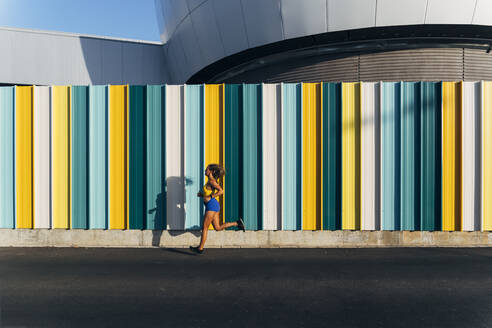 Female jogger in front of colorful wall - MPPF01044