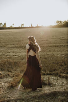 Woman wearing dress walking in field during sunset - GMLF00439