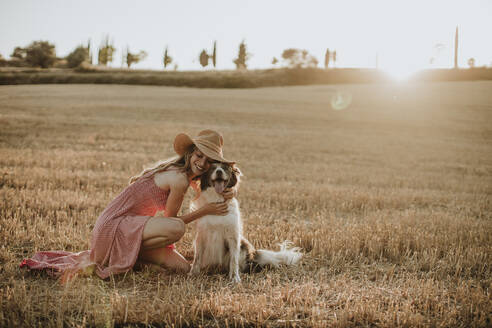 Woman embracing border collie dog in wheat field during sunset - GMLF00457