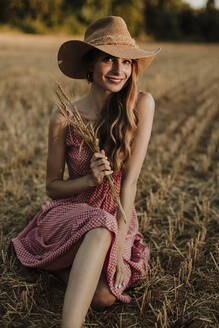 Woman spending leisure time in wheat field during sunset - GMLF00460