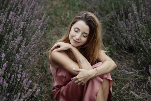Woman sitting in lavender field - GMLF00478
