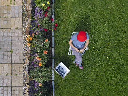 Woman sitting with laptop in garden - KNTF05255