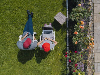 Aerial view of couple sitting in garden - KNTF05258