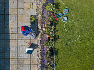 Aerial view of woman sitting on terrace in garden - KNTF05264