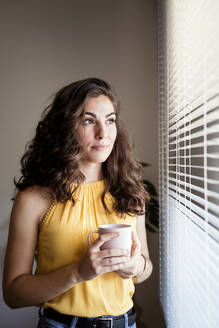 Thoughtful woman holding coffee cup while looking away through blinds at home - EBBF00597