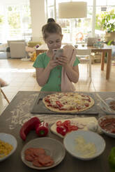 Girl photographing pizza over kitchen island - JOSEF01531