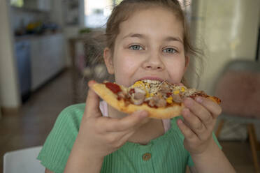 Cute girl eating slice of pizza at home - JOSEF01534