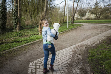 Smiling cute girl with dog walking on footpath - JOSEF01537
