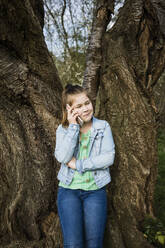 Smiling girl talking on smart phone while standing against tree trunk in park - JOSEF01540