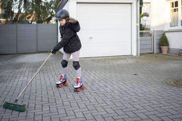 Girl wearing roller skate while cleaning porch - JOSEF01549