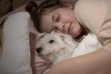 Cute girl holding dog while sleeping in bedroom - JOSEF01552