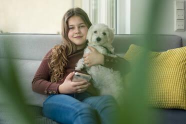 Smiling girl using smart phone while holding dog on sofa - JOSEF01561