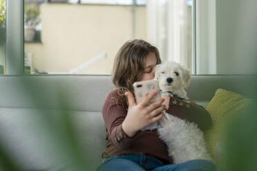 Girl taking selfie through smart phone while kissing dog on sofa - JOSEF01564
