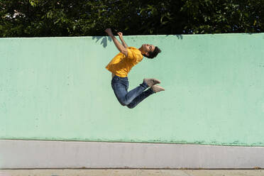 Man jumping mid-air in front of green wall - AFVF06969