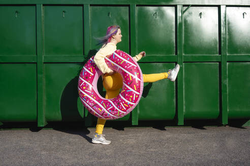 Young woman with dyed hair and floating tyre walking in front of green container - VPIF02868