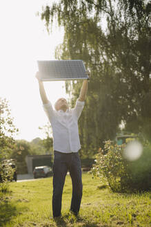 Man holding solar panel above head against clear sky in yard - GUSF04344