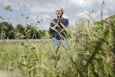 Wrinkled man with hands clasped on grass in agricultural field - GUSF04407